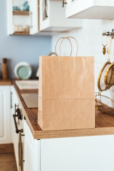 Eco saco de papel de compras em cima da mesa na cozinha moderna. entrega de comida ou conceito de compra do mercado.