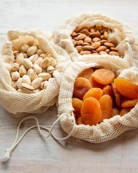 Eco sacolas com pistache, amêndoas e damascos secos em uma superfície de madeira