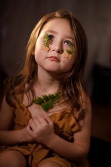 Ecologia, respiração e saúde do conceito de glândula tireóide, retrato de uma menina orando com ramos de samambaia colados com curativo na garganta e no rosto
