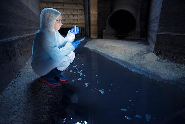 Ecologista colhendo amostra de água do sistema de esgoto e examinando a qualidade e o nível de contaminação e poluição