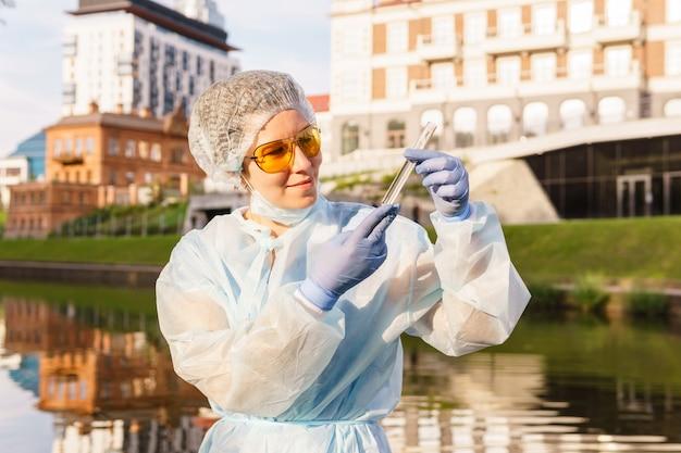 Ecologista ou epidemiologista avalia visualmente a qualidade da água em um rio urbano