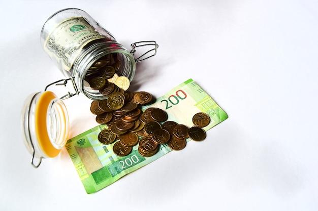 Economia de dinheiro e conceito de orçamento - close-up de moedas e bankton em frasco de vidro na mesa