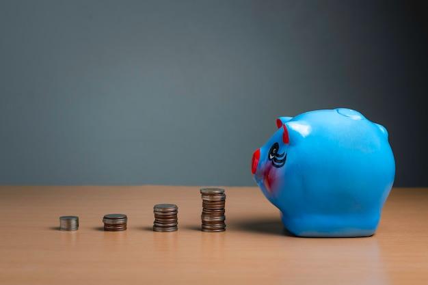 Economia e investimento do cofrinho de moeda, no conceito de fundo, dinheiro e moeda de madeira