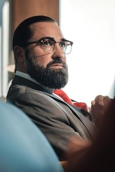 Economista de óculos. economista de cabelos escuros e barbudo usando óculos, sentado no sofá de seu quarto de hotel