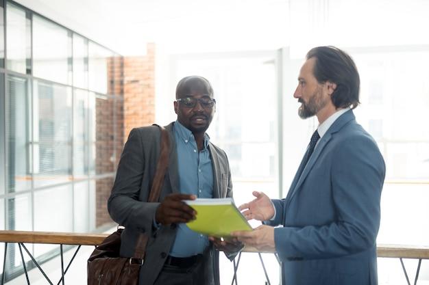 Economista falando. economista de pele escura usando óculos falando com um empresário pela manhã