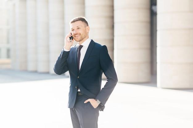 Economista masculino inteligente tem conversa agradável com alguém via telefone inteligente