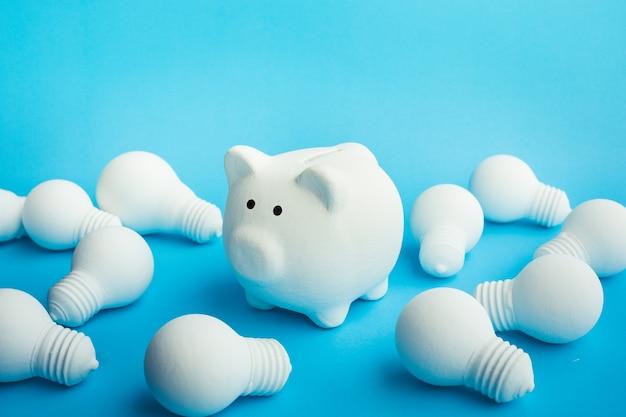 Economizando dinheiro com ideias de conceitos com cofrinho e lâmpada sobre fundo de cor azul