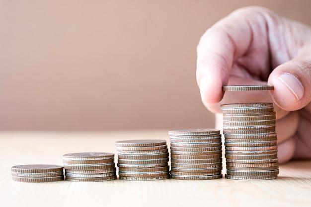Economizando dinheiro e investimento com a mão colocando moedas de dinheiro