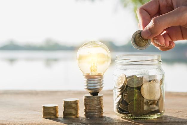 Economizando dinheiro e mão colocando dinheiro moeda no pote de vidro para financeiro e contabilidade.