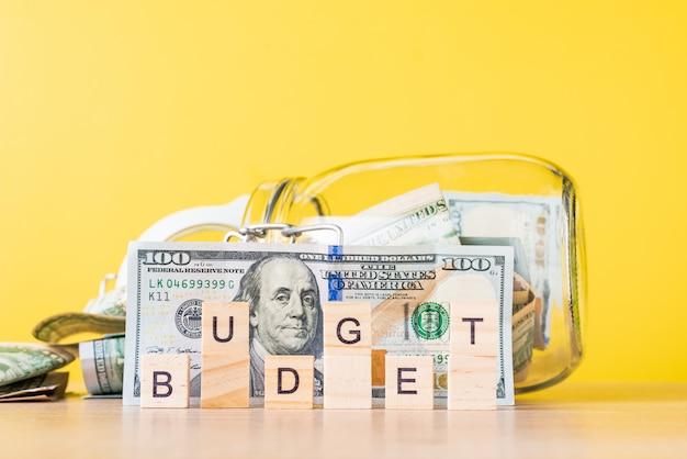 Economizando dinheiro e planejando o conceito de orçamento notas de dólar em vidro, banco de poupança e palavra orçamento