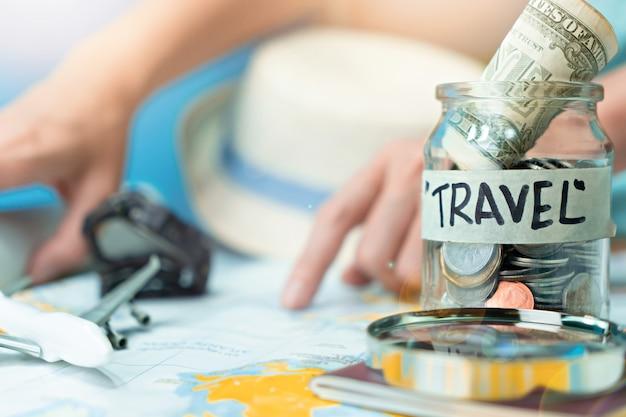 Economizando dinheiro em uma jarra de vidro para viajar no mapa