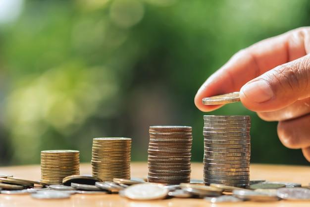Economizando dinheiro mão colocando moedas sobre a pilha na mesa com luz do sol. conceito de finanças e contabilidade