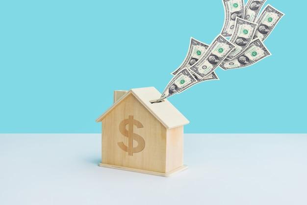 Economizando dinheiro ou conceitos financeiros com o cofrinho e a nota de dólar em casa