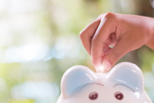 Economizando moedas em um cofrinho de cerâmica conceito de economia de dinheiro um leve borrão
