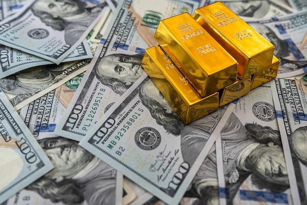 Economizando notas de dólar conceituais com barra de ouro