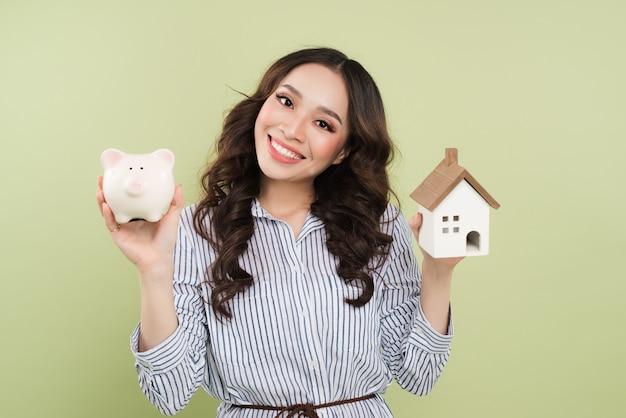 Economizando o conceito de dinheiro. mão segurando o cofrinho e o modelo da casa de madeira