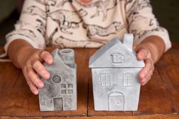Economizando para comprar uma nova casa ou imóveis e empréstimo para planejar o investimento comercial no futuro conceito. mulher sênior com modelo de casa na mesa