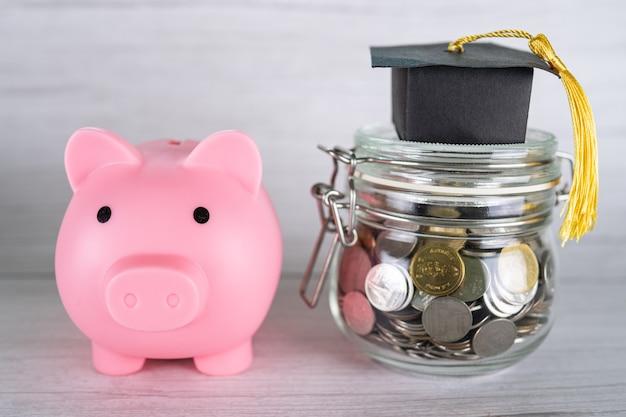 Economize moedas de dinheiro no frasco de grama com cofrinho e chapéu de formatura, conceito de educação de finanças empresariais.