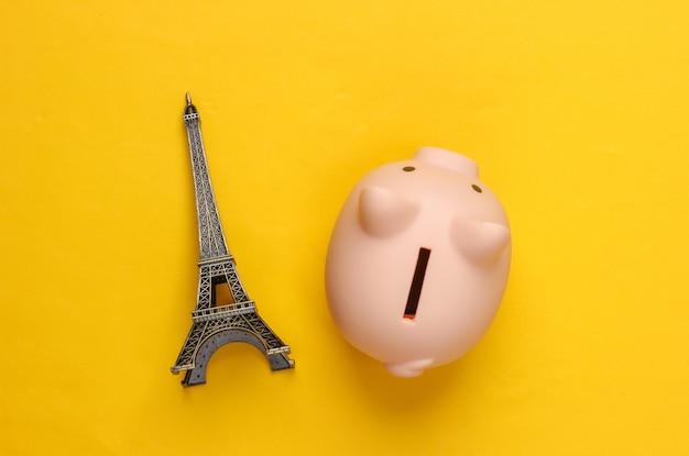 Economize para uma viagem. cofrinho com uma figura da torre eiffel em amarelo