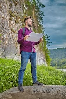 Ecoturismo, jovem barbudo com mochila nas costas, em pé sobre uma rocha com mapa topográfico nas mãos e explorando a vizinhança, ele se dedica a caminhadas no verão.