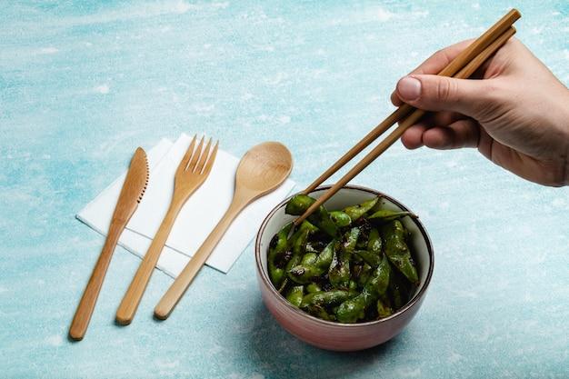 Edamame cozido em uma mesa azul. lanche de vagens de soja