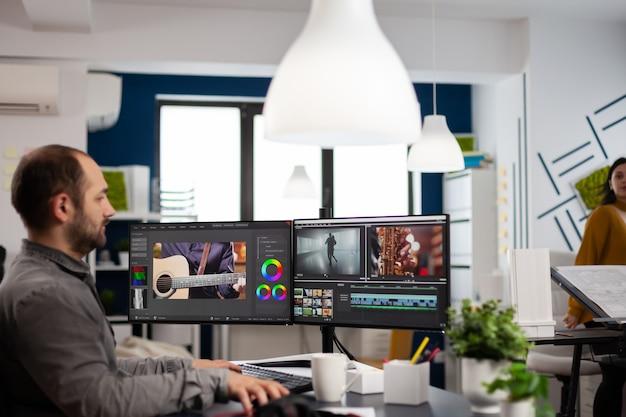 Edição de cinegrafista, corte de filmagem e som no computador com configuração de monitores duplos trabalhando em escritório de agência de criação