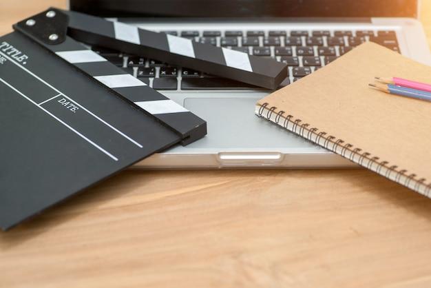 Edição de vídeo, claquete de cinema laptop e lápis de bloco de notas sobre a mesa de madeira vista superior shot.dark