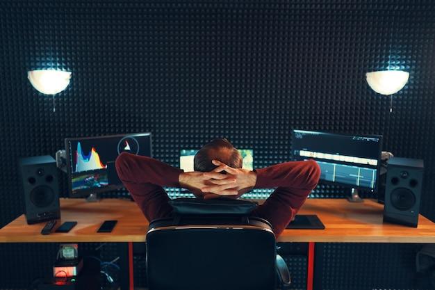 Edição de vídeo. editor profissional adicionando efeitos sonoros especiais. vista traseira do jovem vendo gráficos em monitores. copie o espaço na parede cinza