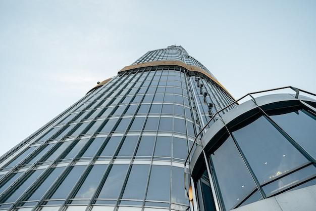 Edifício alto de vidro com vista do céu azul da parte inferior