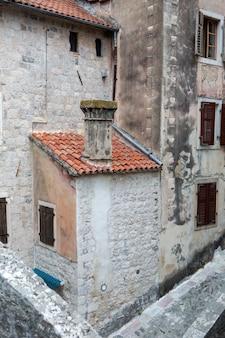 Edifício antigo em montenegro com janelas, venezianas e hera