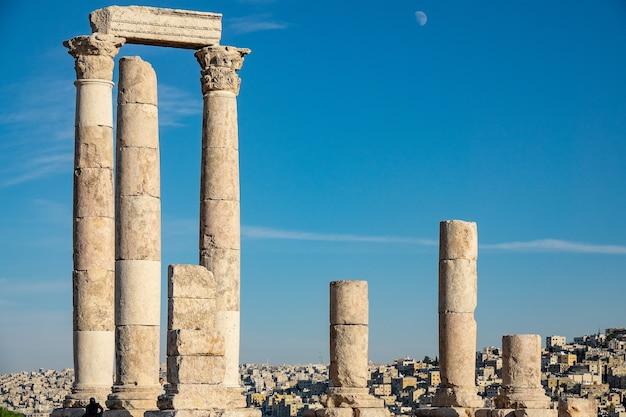 Edifício antigo em ruínas feito de grandes torres e rochas sob um céu claro