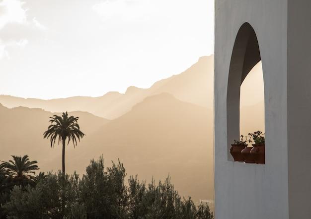 Edifício branco com janela em arco com plantas, palmeiras e montanhas