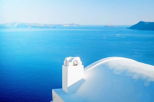 Edifício branco contra o céu azul e o mar na ilha de santorini, oia, grécia