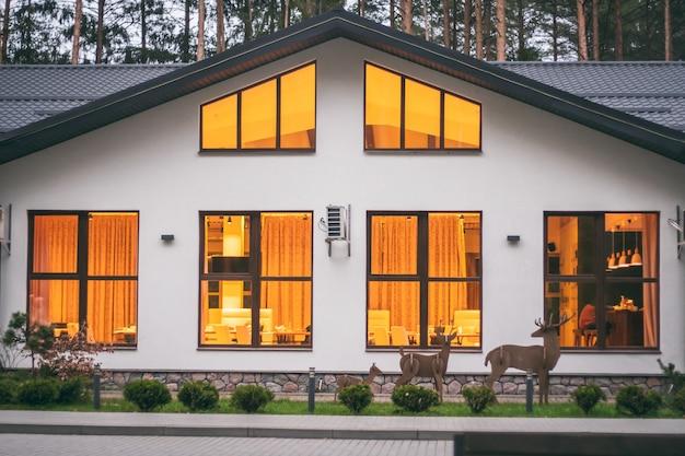Edifício branco de restaurante com telhado de duas águas em floresta de pinheiros, com luzes acesas em grandes janelas