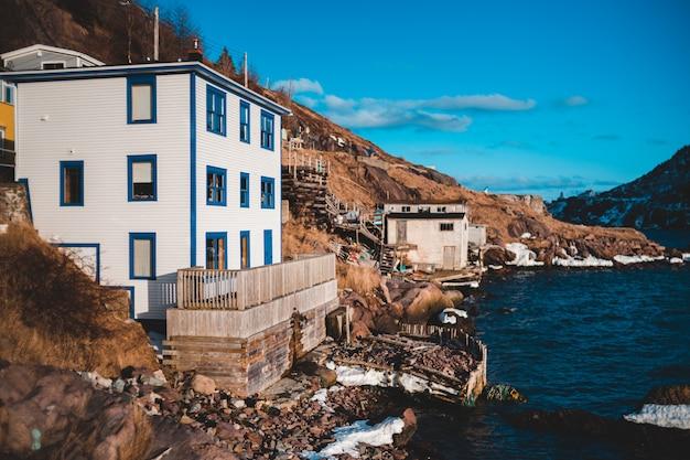 Edifício branco de três andares ao lado do mar