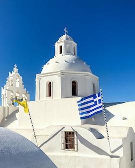 Edifício branco do templo com uma torre de sino na ilha santorini.