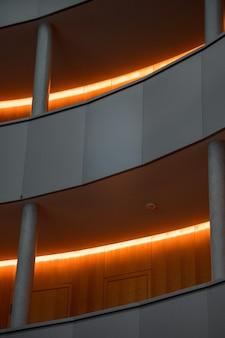 Edifício cinza com luzes de corredor acesas