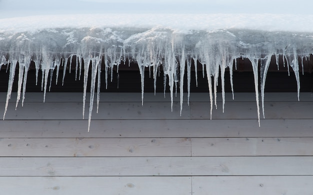 Edifício coberto com pingentes, closeup. estalactite de gelo pendurado no telhado, copie o espaço