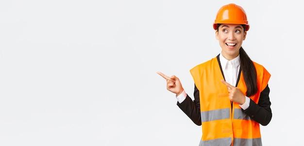 Edifício, construção e conceito industrial. animado e interessado, um arquiteto asiático sorridente, engenheiro de capacete e roupas de segurança, olhando, apontando o canto superior esquerdo para um projeto interessante