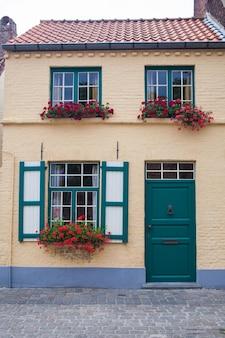 Edifício da cidade velha com porta e flores na janela