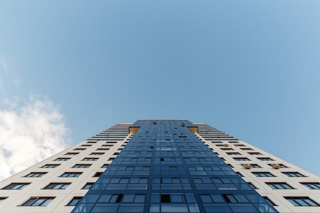 Edifício de apartamentos alto contra o céu azul. vista de baixo.