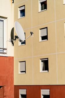 Edifício de apartamentos com antena parabólica perto da janela, close-up