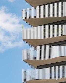Edifício de concreto cinza com grades de metal branco sob o céu azul