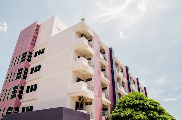 Edifício de dormitório roxo com fundo de céu azul.