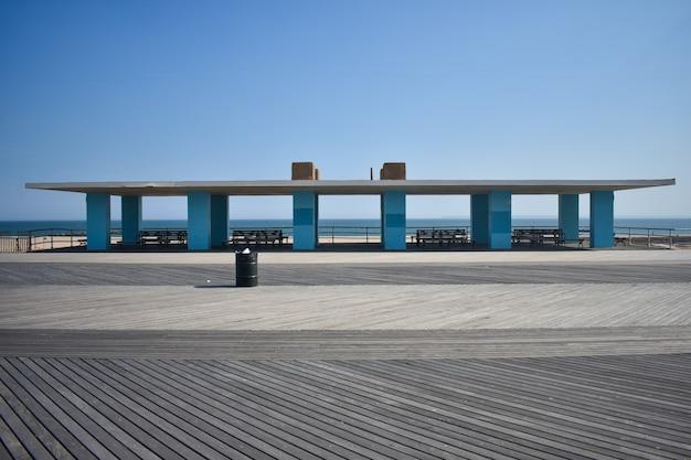 Edifício de dossel na praia com colunas azuis, telhado branco e bancos