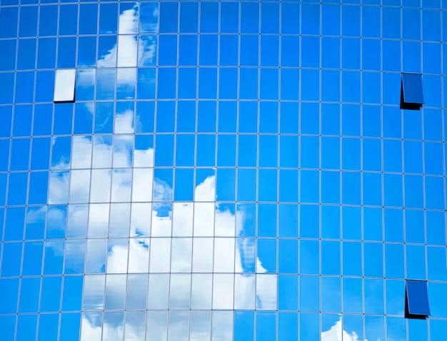 Edifício de vidro highrise com céu e nuvens de reflexão