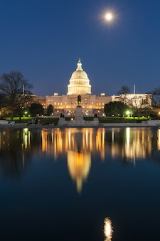 Edifício do capitólio dos estados unidos na hora do crepúsculo com reflexo super da lua cheia com a grande piscina