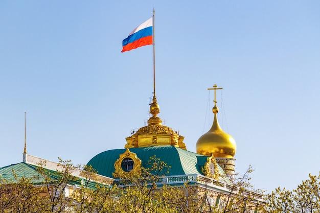Edifício do grande palácio do kremlin com a bandeira da federação russa acenando no telhado contra a cúpula dourada da igreja em uma manhã ensolarada