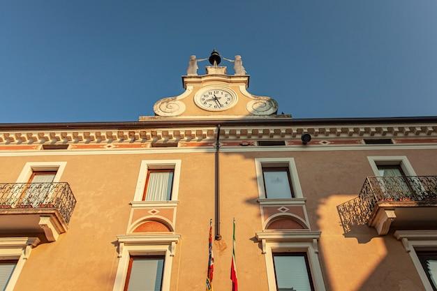 Edifício histórico com relógio em bardolino, na itália, ao pôr do sol