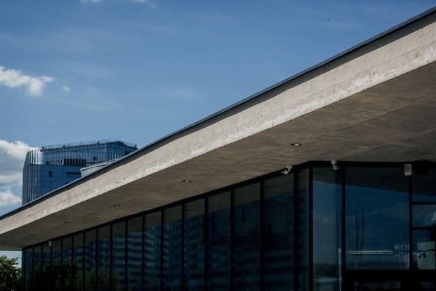 Edifício moderno com janelas e telhado de concreto contra o céu.